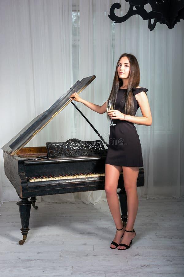 Meisje dichtbij de piano met een glas wijn royalty-vrije stock afbeeldingen