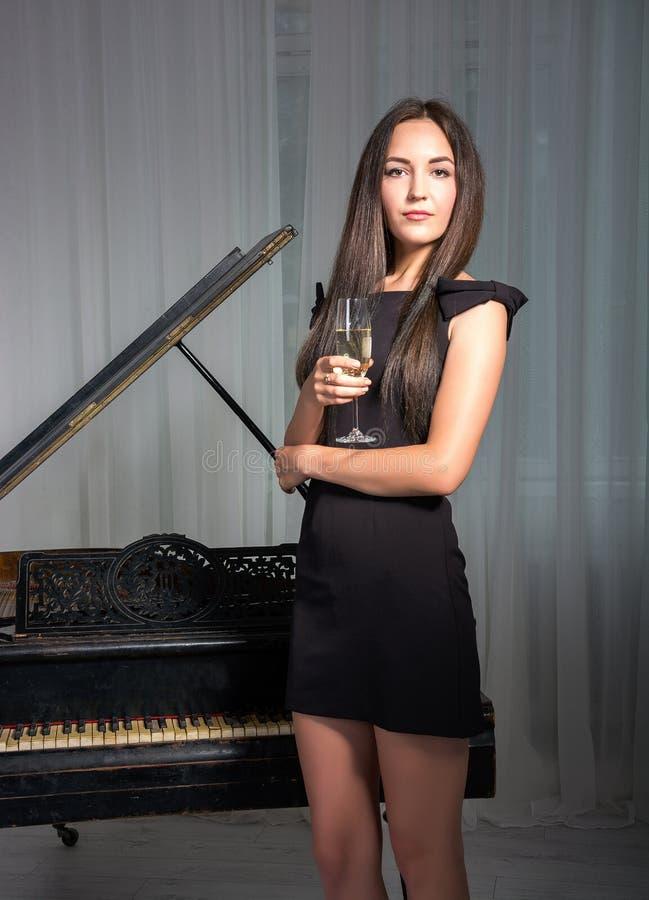 Meisje dichtbij de piano met een glas wijn stock afbeeldingen