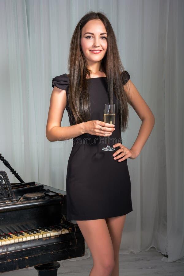 Meisje dichtbij de piano met een glas wijn stock fotografie