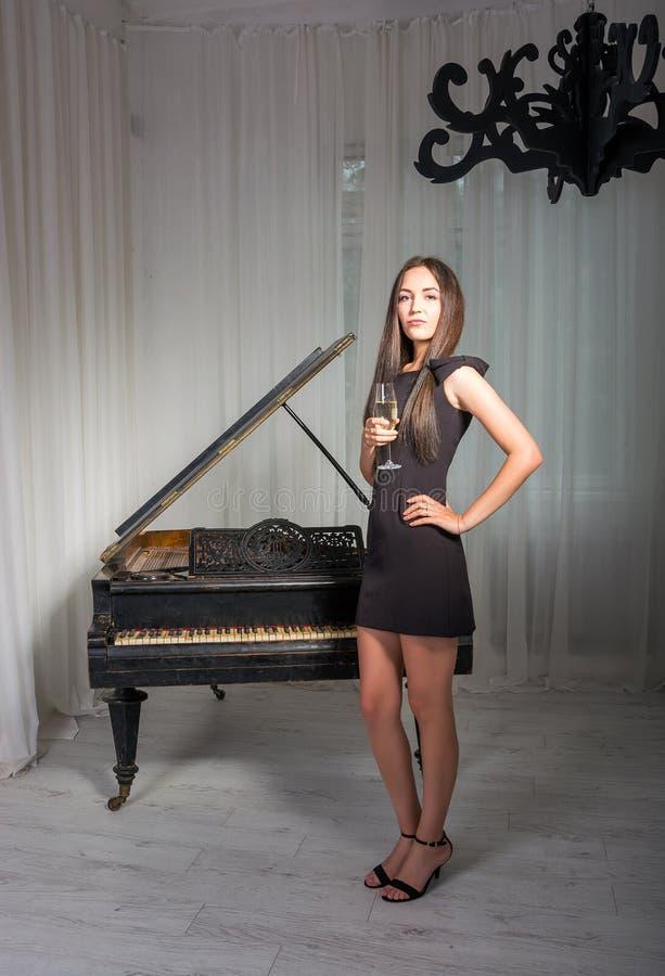 Meisje dichtbij de piano met een glas wijn stock foto