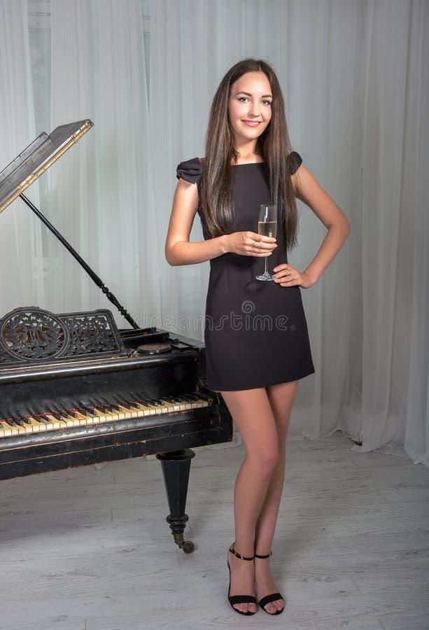 Meisje dichtbij de piano met een glas wijn royalty-vrije stock foto