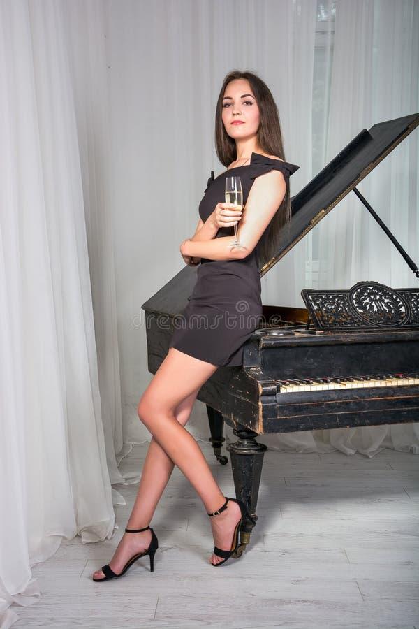 Meisje dichtbij de piano met een glas wijn stock afbeelding