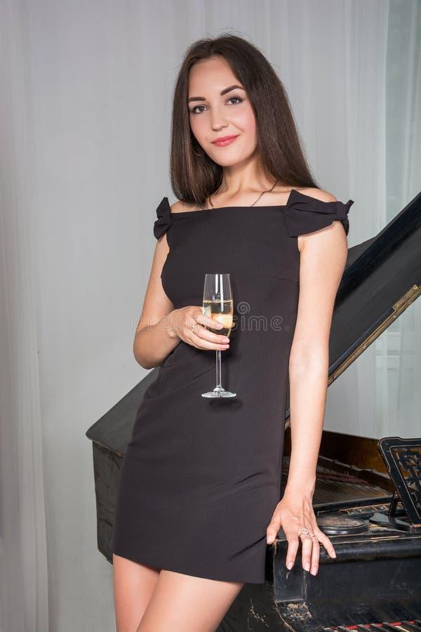 Meisje dichtbij de piano met een glas wijn royalty-vrije stock foto's