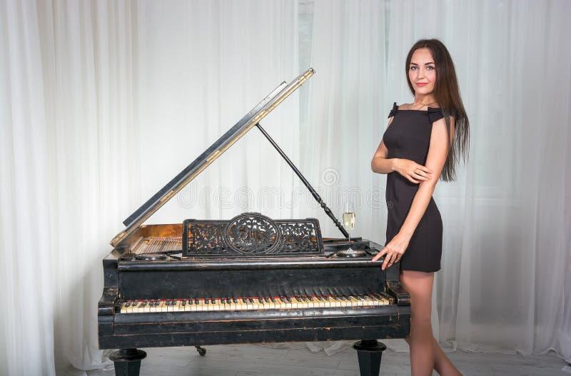 Meisje dichtbij de retro piano met een glas wijn stock afbeelding