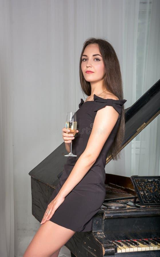 Meisje dichtbij de retro piano met een glas wijn royalty-vrije stock afbeelding