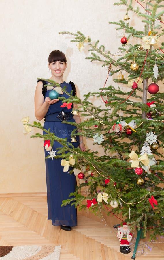 Meisje dichtbij een boom van het Nieuwjaar stock afbeeldingen