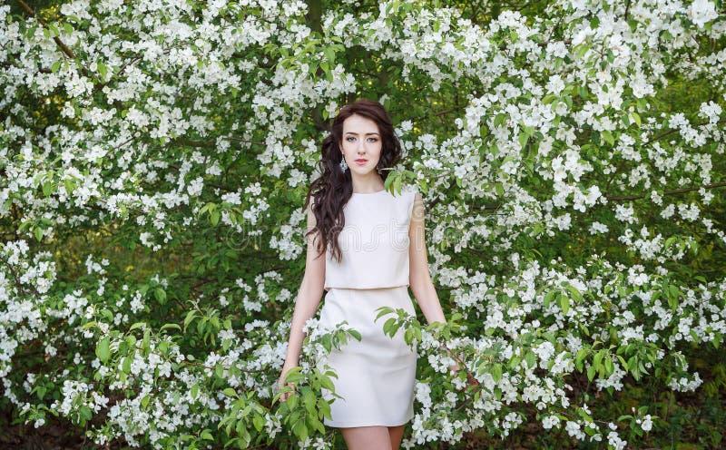 Meisje dichtbij een struik van witte bloemen stock afbeelding