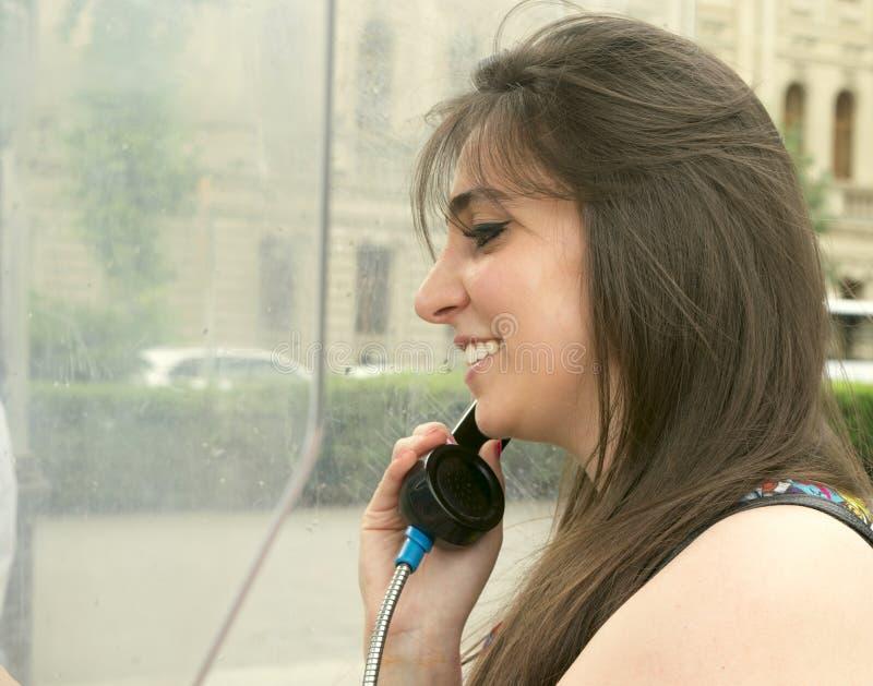 Meisje dichtbij een telefooncel stock afbeelding