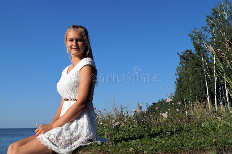 Meisje dichtbij het overzees op de achtergrond van blauwe hemel stock foto's