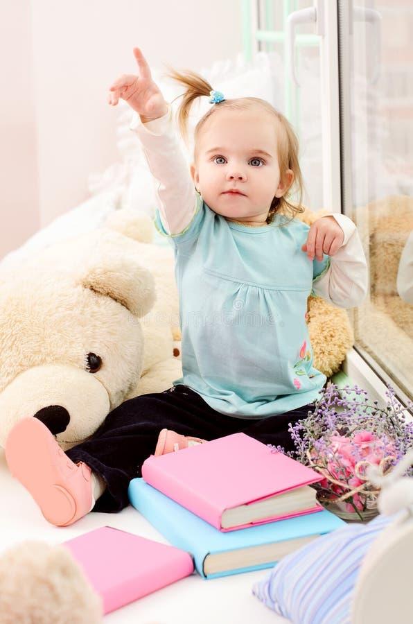 meisje dichtbij het venster met boeken stock afbeeldingen