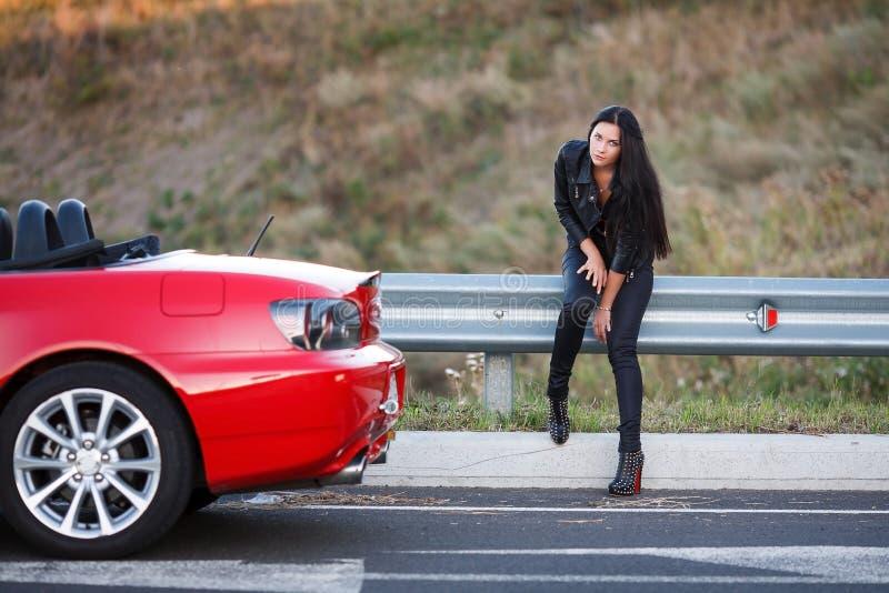 Meisje dichtbij rode auto stock foto