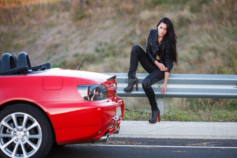 Meisje dichtbij rode auto royalty-vrije stock foto