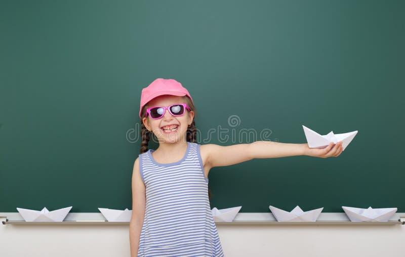 Meisje dichtbij schoolraad met document vliegtuig en boot stock afbeeldingen