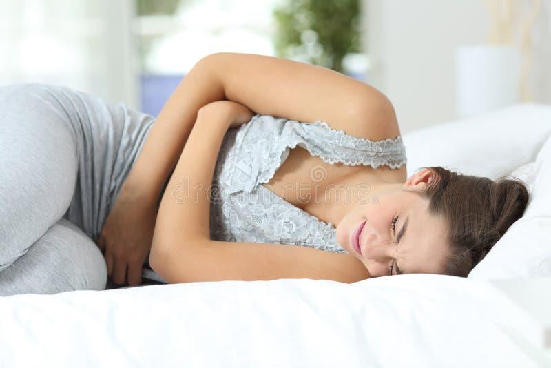 Meisje die aan menstruele pijnen op het bed lijden stock foto's