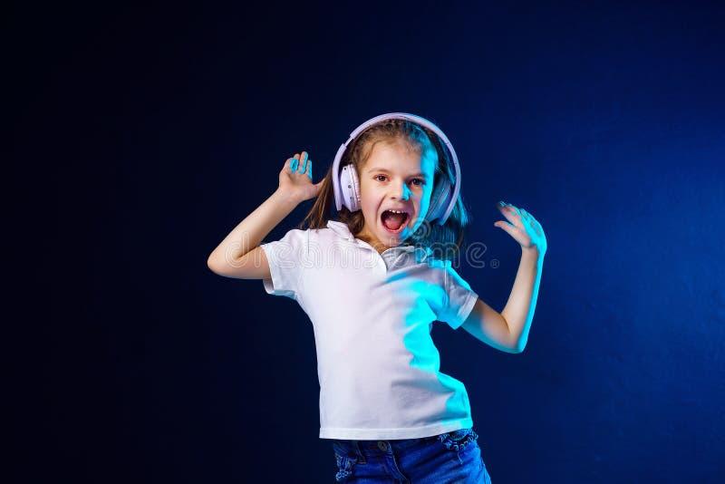Meisje die aan muziek in hoofdtelefoons op donkere kleurrijke achtergrond luisteren Leuk kind die dans van muziek genieten, die c stock foto's
