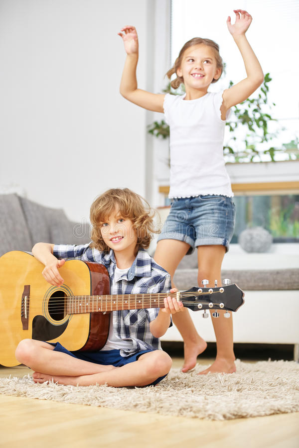 Meisje die aan muziek van jongen het spelen gitaar dansen stock fotografie