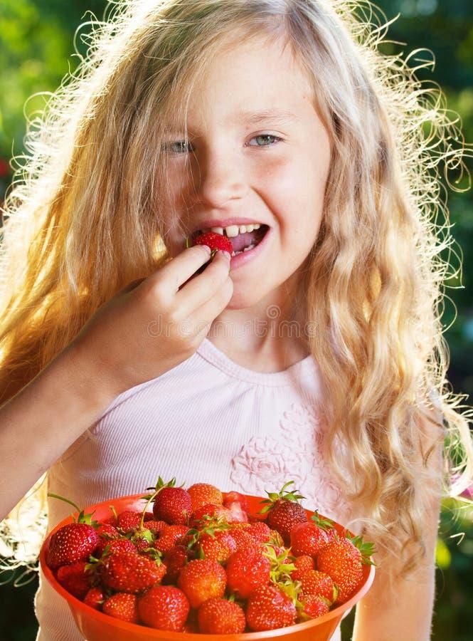 Meisje die aardbei eten royalty-vrije stock afbeeldingen