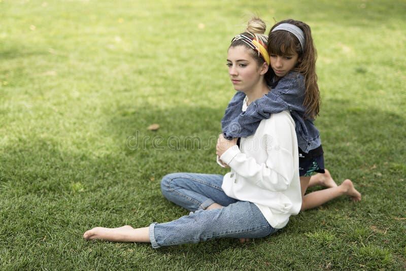 Meisje die achter haar zuster koesteren royalty-vrije stock afbeelding