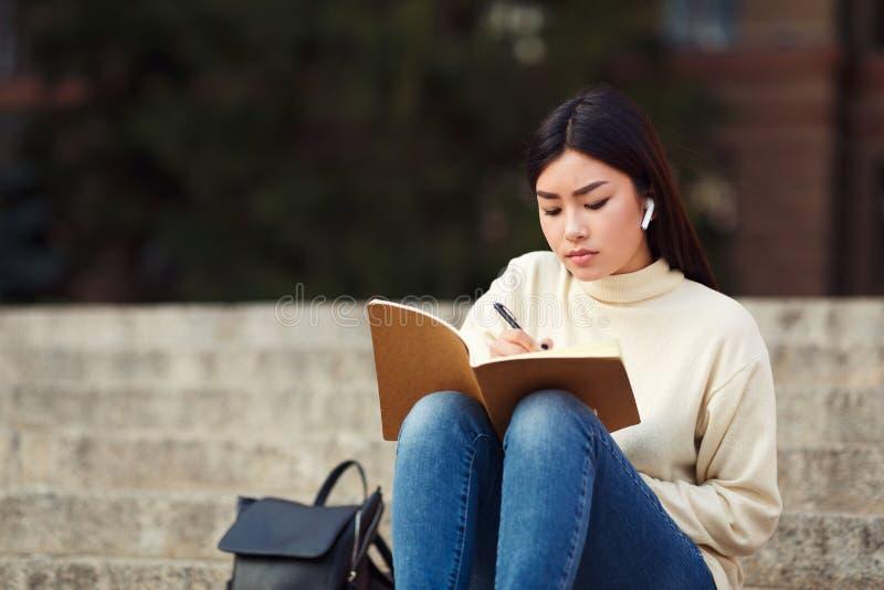 Meisje die in airpods in agenda schrijven, die voor lezing voorbereidingen treffen stock afbeeldingen