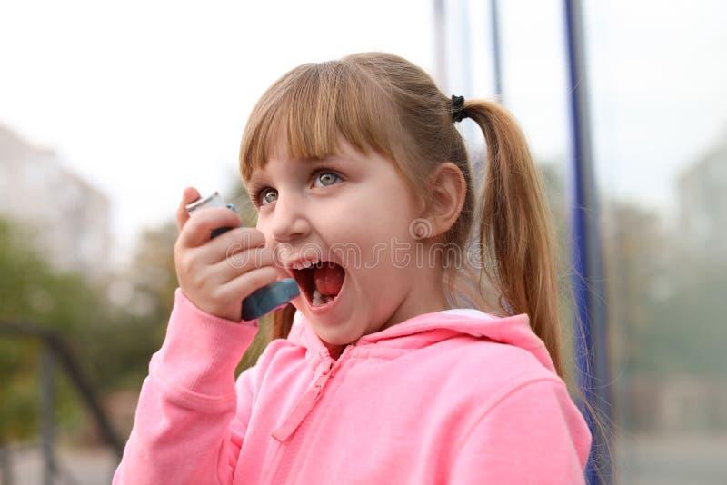 Meisje die astmainhaleertoestel in openlucht met behulp van royalty-vrije stock foto's