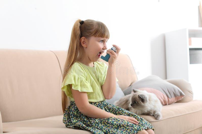 Meisje die astmainhaleertoestel thuis met behulp van dichtbij kat royalty-vrije stock fotografie