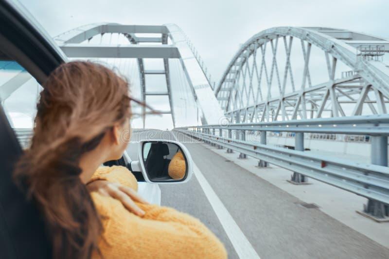 Meisje die in auto vooruit op een brug de reis van de weekendweg bekijken royalty-vrije stock fotografie