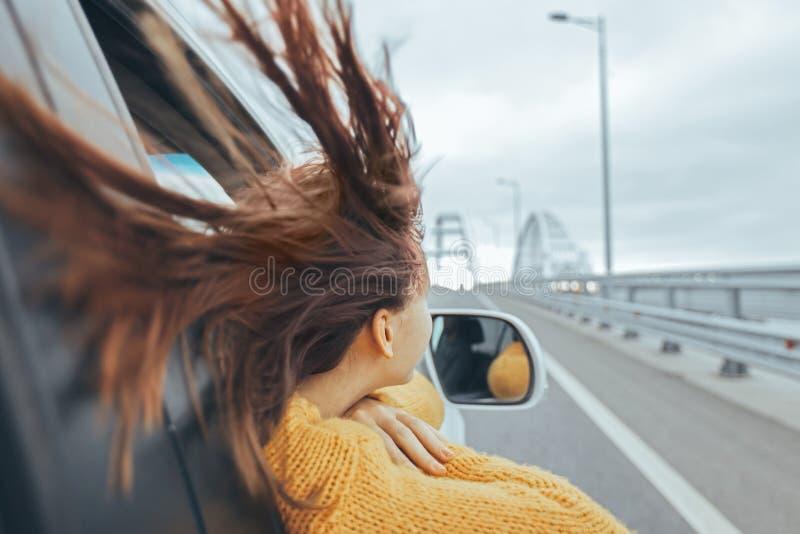 Meisje die in auto vooruit op een brug de reis van de weekendweg bekijken stock foto's