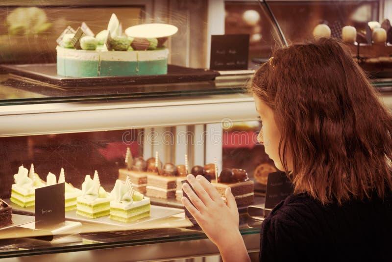 Meisje die in banketbakkerijwinkel de vertoning bekijken Zoet royalty-vrije stock fotografie