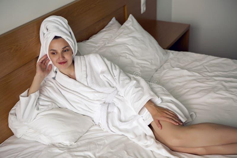 Meisje die in bed in een Badjas thuis liggen stock afbeeldingen