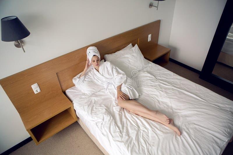 Meisje die in bed in een Badjas thuis liggen stock afbeelding
