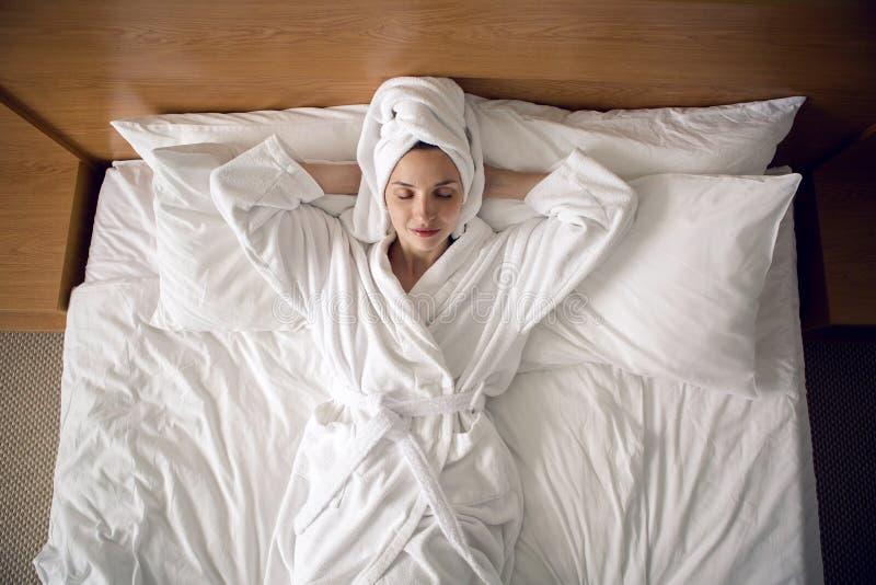 Meisje die in bed in een Badjas thuis liggen royalty-vrije stock foto