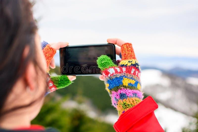 Meisje die beeld van de winterlandschap nemen met een slimme telefoon stock afbeeldingen