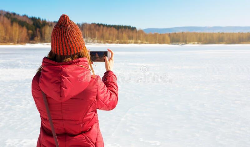 Meisje die beeld van een bevroren meer met telefoon nemen stock fotografie