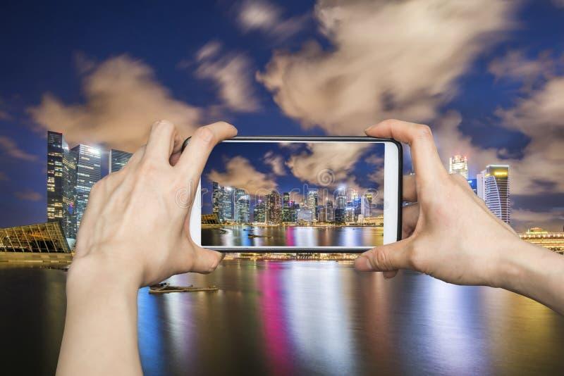 Meisje die beelden op mobiele slimme telefoon in Singapore nemen cityscap stock foto's