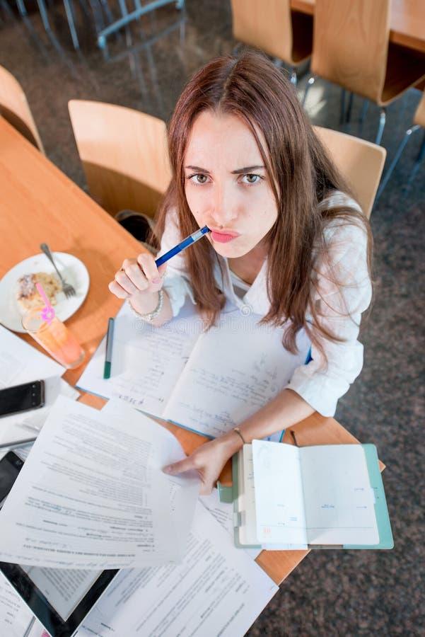 Meisje die bij de Universitaire kantine bestuderen stock afbeelding