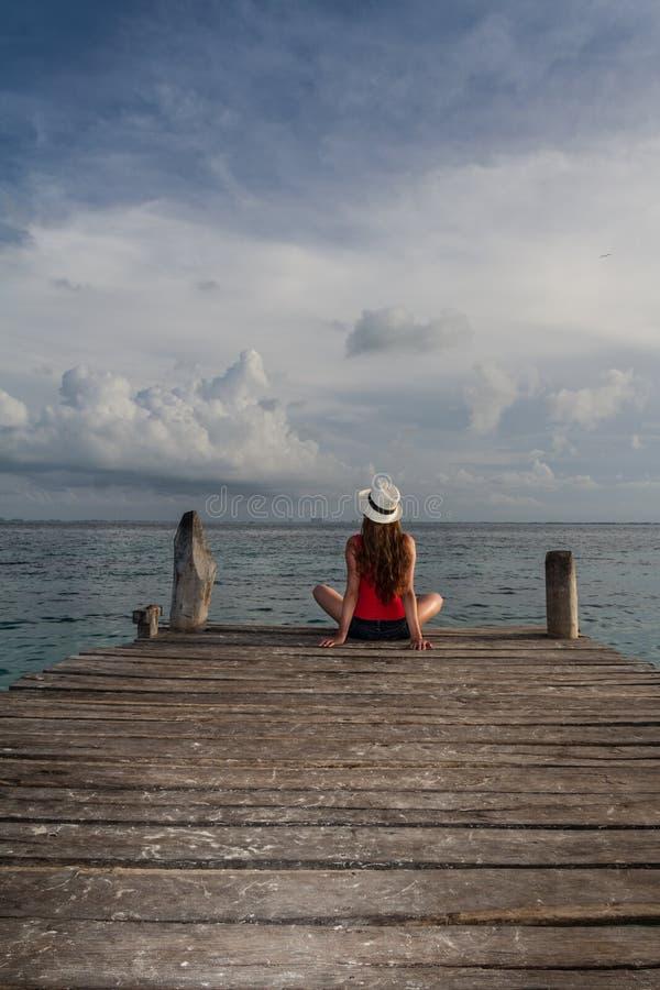 Meisje die bij het strand mediteren stock afbeelding