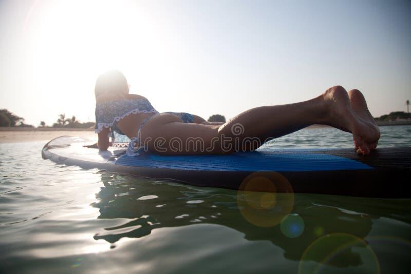 Meisje die bij zonsondergang surfen stock afbeelding