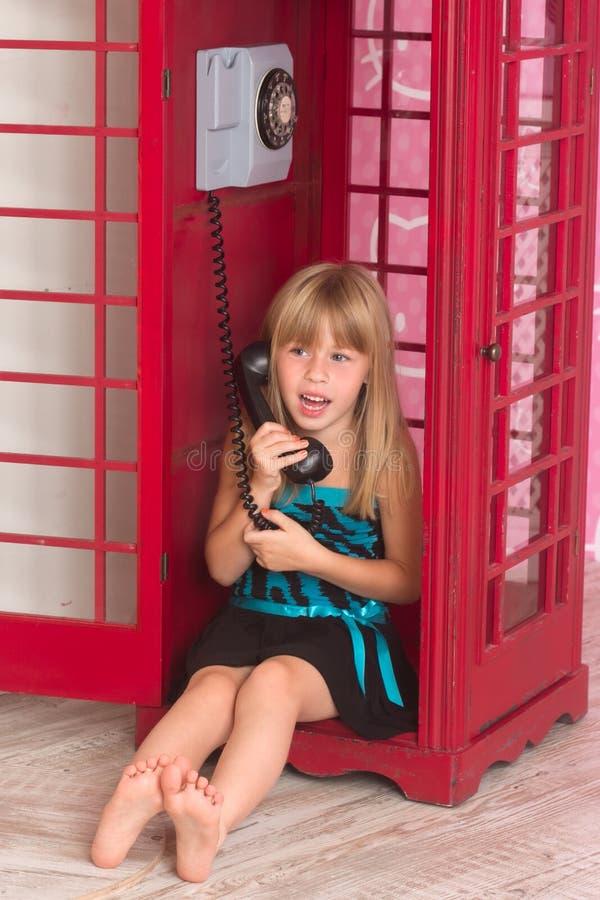 Meisje die binnen rood roepen een telefoon stock foto's