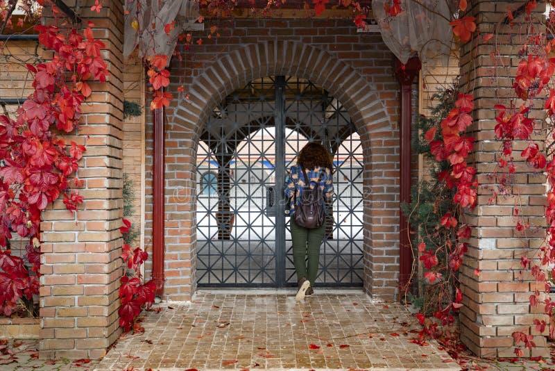 Meisje die binnen van Decoratieve overspannen ijzergateway door baksteendeur kijken royalty-vrije stock fotografie