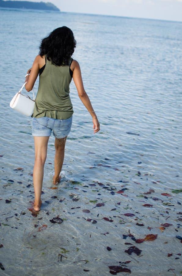 Meisje die boos met haar Zak op een Strand lopen stock afbeelding