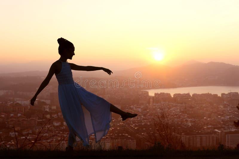Meisje die bovenop berg dansen die de stad overzien stock afbeeldingen