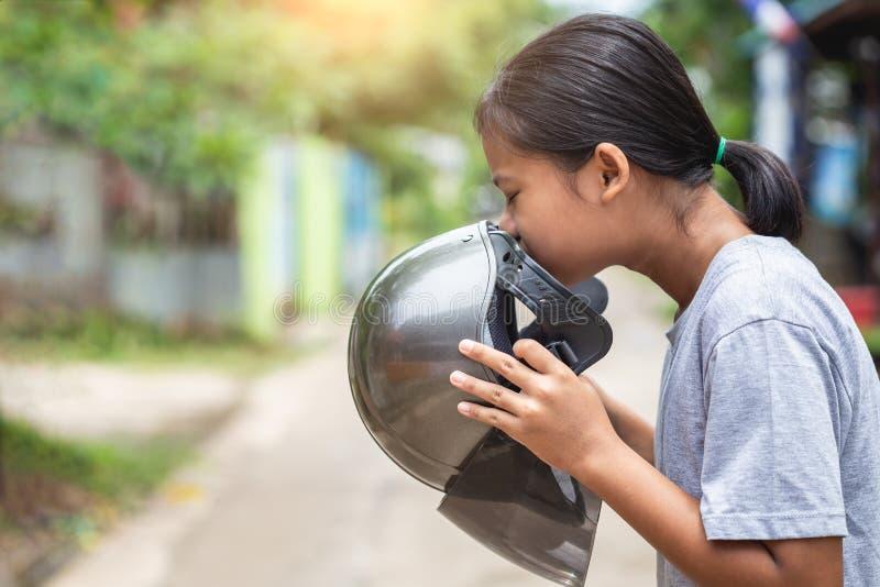 Meisje die bruine helm van motorfiets en het ruiken houden Oude helm royalty-vrije stock fotografie