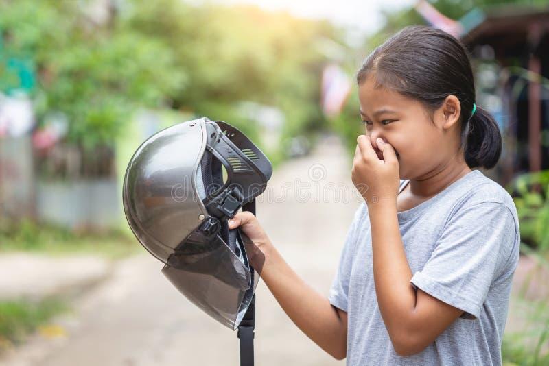 Meisje die bruine helm van motorfiets en het ruiken houden Oude helm stock fotografie