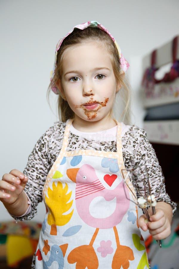 Meisje die chocolade eten van de mixerklopper royalty-vrije stock afbeeldingen