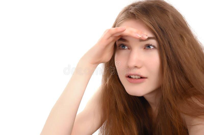 Meisje die de hand houden bij haar voorhoofd die ver eruit zien stock foto
