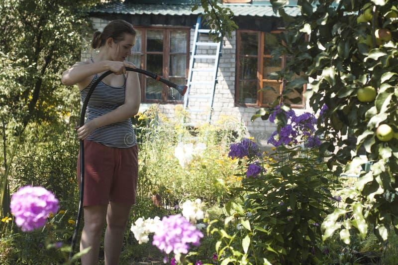 Meisje die de installaties water geven stock fotografie