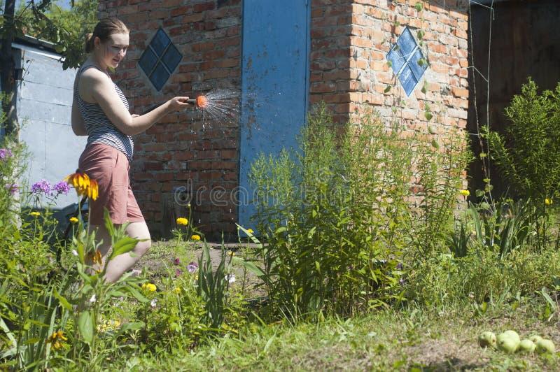 Meisje die de installaties water geven stock afbeelding