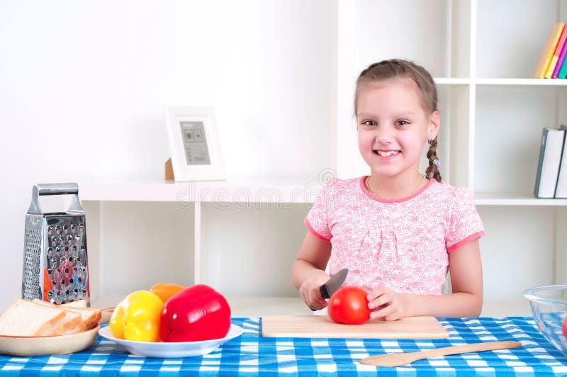 Meisje die in de keuken scherpe groenten werken stock foto's