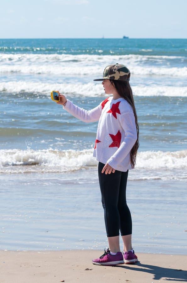 Meisje die de kust van Overzees op uw mobiele telefoon fotograferen stock afbeelding