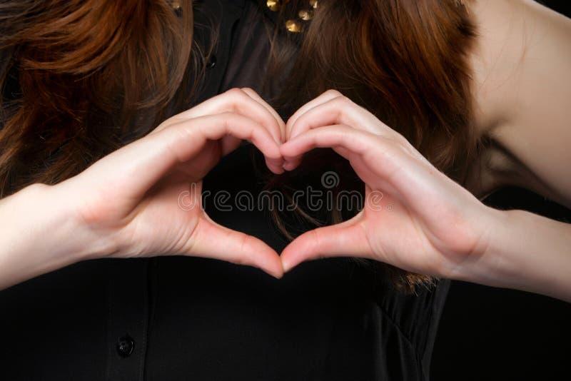 Meisje die de liefdesymbool van de hartvorm met haar handen doen. royalty-vrije stock foto